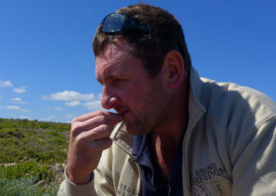 Karel Du Toit probiert eine Blumenwurzel, die er ausgegraben hat.